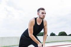 Atleta que se prepara para entrenar o las competencias en pista corriente fotos de archivo