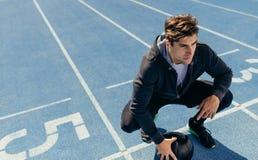 Atleta que se sienta en la pista corriente con una bola de medicina Imágenes de archivo libres de regalías