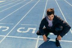 Atleta que se sienta en la pista corriente con una bola de medicina Imagen de archivo