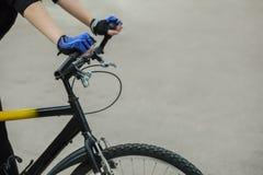 Atleta que sostiene el manillar de las manos En las manos puestos de guantes azules cycling foto de archivo