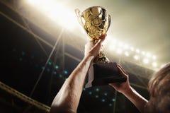 Atleta que sostiene la taza del trofeo en la noche fotografía de archivo libre de regalías