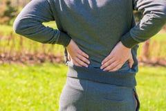 Atleta que sostiene más de espalda dolorido de las manos Fotografía de archivo libre de regalías