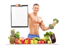 Atleta que sostiene una pesa de gimnasia del bróculi y un tablero Fotos de archivo libres de regalías