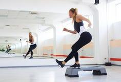 Atleta que tiene aeróbicos del paso en un gimnasio Foto de archivo libre de regalías