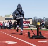 Atleta que tira de un trineo con los pesos en una pista Imagen de archivo libre de regalías