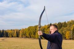 Atleta que visa um alvo e tiros uma seta archery fotografia de stock
