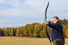 Atleta que visa um alvo e tiros uma seta archery imagem de stock
