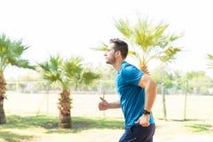 Atleta resuelto Running On Sunny Day In Park fotos de archivo libres de regalías