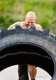 Atleta risoluto Doing Tire-Flip Exercise Fotografie Stock