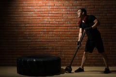Atleta robi ćwiczeniu z młotem i oponą w gym na ściana z cegieł tle obraz royalty free