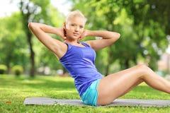 Atleta rubio joven que hace ejercicios en una estera en un parque Imágenes de archivo libres de regalías
