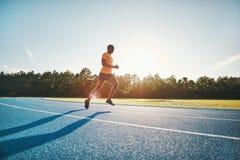 Atleta solitario que corre a lo largo de una pista en un día soleado imagenes de archivo