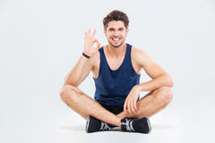 Atleta sonriente del hombre joven que sienta y que muestra la muestra aceptable Fotos de archivo libres de regalías