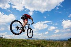 Atleta sportowa rowerzysta w fachowym sportswear lataniu w powietrzu na jego przecinającego kraju rowerze fotografia stock