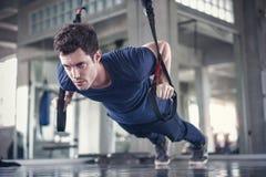 Atleta sporty mężczyzna robi ćwiczeniu z sprawności fizycznej trx patkami umacniać jego brzusznego mięsień w gym zdjęcie stock