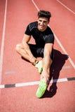 Atleta stanco che si siede sulla pista corrente Fotografia Stock