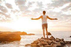 Atleta stoi backwards z rękami podnosić przy skalistą plażą Obraz Stock