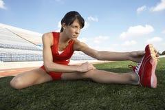 Atleta Stretching On Field imagem de stock