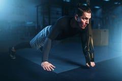 Atleta su addestramento, esercizio di piegamento sulle braccia con la corda Fotografia Stock
