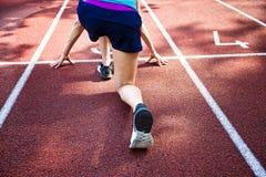 Atleta sulla linea di partenza che aspetta l'inizio in pista corrente Immagini Stock Libere da Diritti