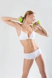 Atleta sveglio della ragazza su un fondo bianco Fotografia Stock