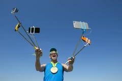 Atleta Taking Selfies da medalha de ouro com varas de Selfie Fotos de Stock Royalty Free
