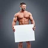 Atleta trzyma pustego białego plakat z mięśniami zdjęcie stock