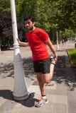 Atleta urbano che fa allungamento accanto ad un palo della luce Fotografia Stock Libera da Diritti