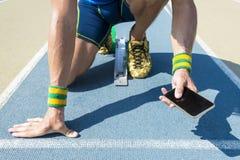 Atleta Using Mobile Phone en la pista Imagen de archivo libre de regalías