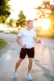 Atleta w białym skrótu biegaczu w wieczór i koszulce, jogging Mężczyzna w parku słucha audiobook, a Obrazy Royalty Free