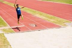 Atleta wykonuje skok w dal Zdjęcie Stock