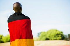 Atleta z niemiec flaga zawijającą wokoło jego ciała Zdjęcia Stock