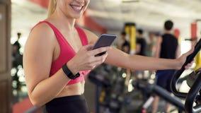 Atleta z sprawności fizycznej bransoletki ćwiczenia jeździeckim rowerem i gawędzenie na telefonie komórkowym obraz stock