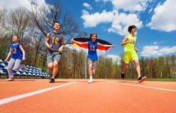 Atletas adolescentes con la bandera alemana que corre en pista Fotos de archivo
