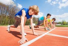 Atletas adolescentes que se preparan para comenzar a correr Foto de archivo