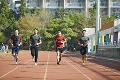 Atletas asiáticos jovenes que corren en pista Imagen de archivo libre de regalías