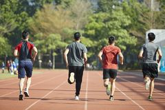 Atletas asiáticos jovenes que corren en pista Imágenes de archivo libres de regalías