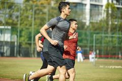 Atletas asiáticos jovenes que corren en pista Fotografía de archivo