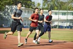 Atletas asiáticos jovenes que corren en pista Imagenes de archivo