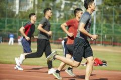 Atletas asiáticos jovenes que corren en pista Imagen de archivo