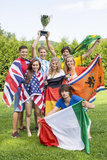Atletas con las diversas banderas nacionales que celebran en parque Fotografía de archivo