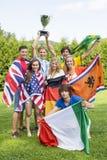 Atletas con las diversas banderas nacionales que celebran en parque Imagenes de archivo