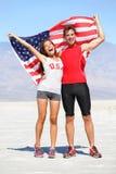Atletas de la gente que animan que sostienen la bandera americana de los E.E.U.U. Foto de archivo libre de regalías
