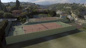 Atletas de sexo femenino y de sexo masculino profesionales que juegan al tenis, visión aérea, entrenando almacen de video