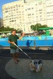 Atletas do cumprimento do residente local que competem na estrada de ciclismo olímpica do Rio 2016 na praia de Copacabana Fotografia de Stock Royalty Free