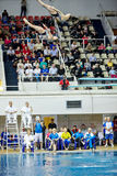 Atletas durante competencias en el salto syncronized del trampolín Fotografía de archivo