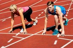 Atletas en la línea de salida en circuito de carreras Foto de archivo