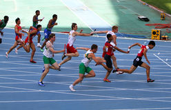 Atletas en los 4 x 100 contadores de la raza de relais Imagenes de archivo