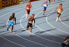 Atletas en los 4 x 100 contadores de la raza de relais Imágenes de archivo libres de regalías