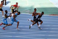 Atletas en los 4 x 100 contadores de la raza de relais Foto de archivo